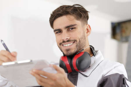 Trabajador sonriente en uniforme de protección escribiendo en el portapapeles Foto de archivo