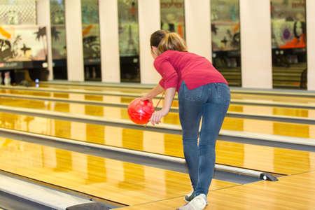 Frau wirft Ball im Bowlingclub