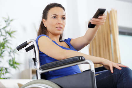 disabled woman in wheelchair watching movies at home Zdjęcie Seryjne