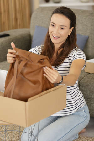 satified woman unpacking new bag from a cardboard box