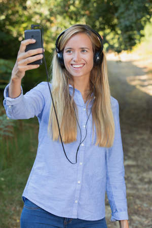 woman walking in the countryside taking selfie with smartphone