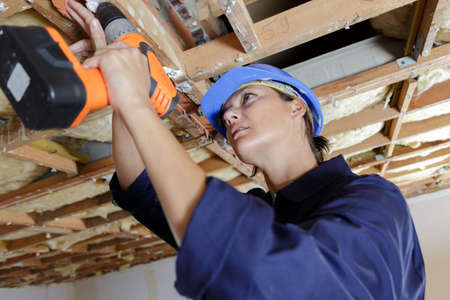 female builder using drill on wooden trusses