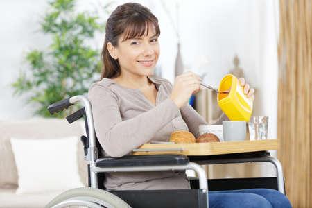 smiling woman sitting in a wheel chair having breakfast