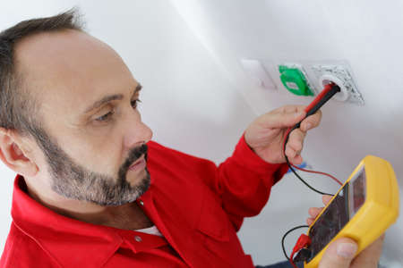 electrician testing plug socket with multimeter