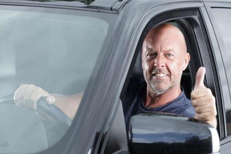 man in een auto met duimen omhoog