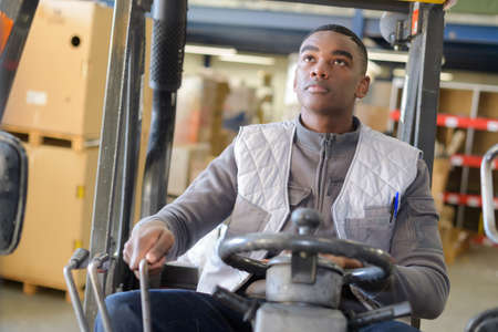 Man driving forklift in warehouse for diy equipment Zdjęcie Seryjne