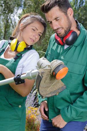 Gardeners checking a garden tool