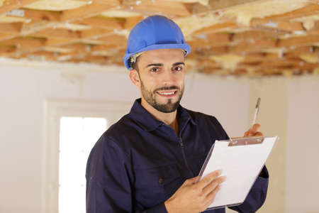 Man holding clipboard in property