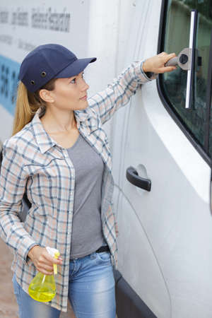 Woman cleaning a car window