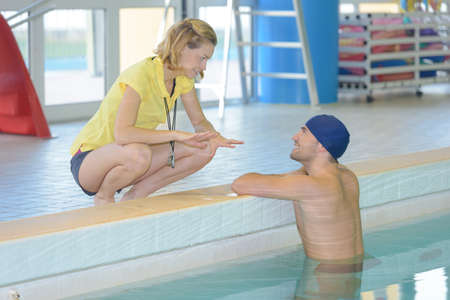 Young fit trainer talking to swimmer in leisure center