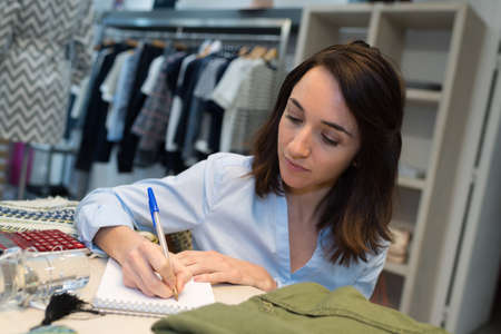 Young female fashion store worker writing notes