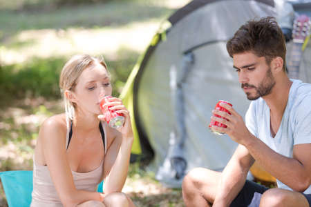 Young couple traveling and drinking soda