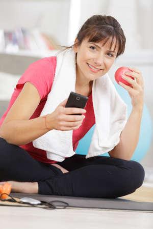 Woman using smart phone and holding apple Zdjęcie Seryjne