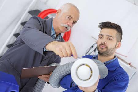Men holding parts of ventilation system
