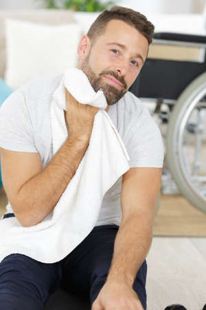 Tired sportsman wiping face by towel at gym locker room