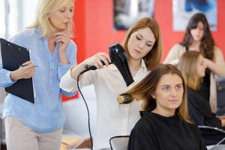 Female apprentice hairdresser training with customer Zdjęcie Seryjne