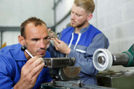 Auto repairman grinding autobody piece of acar