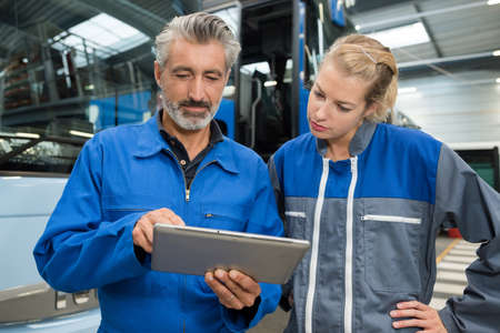 Man and woman using tablet to fix car