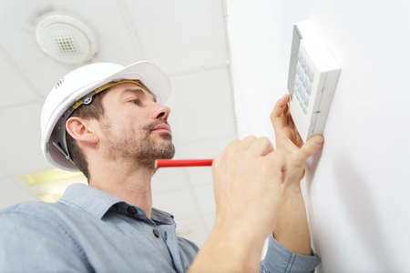 Worker adjusts digital thermostat Zdjęcie Seryjne