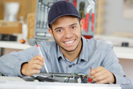 Young serviceman repairing washing machine Zdjęcie Seryjne