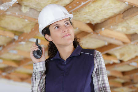 Young female construction worker using walkie talkie on site