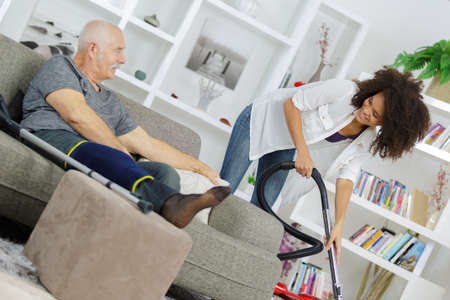 Young woman assisting senior while he is on the sofa Zdjęcie Seryjne