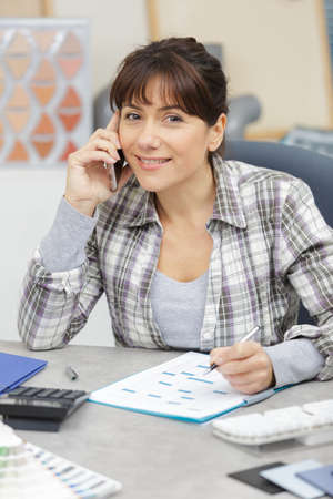 Smiling businesswoman or helpdesk operator with headset in an office