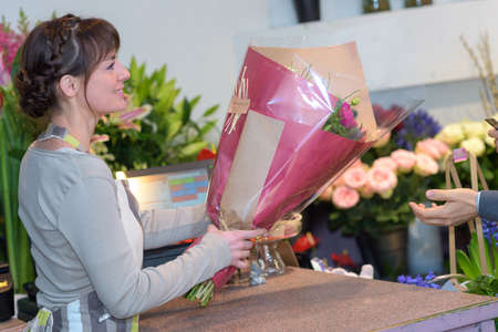 Young female florist giving the bouquet to the client Zdjęcie Seryjne