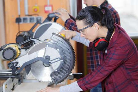 Young female carpenter using a circular saw Zdjęcie Seryjne