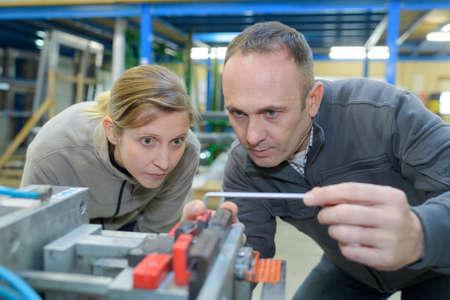 Man and woman looking at metal component Zdjęcie Seryjne