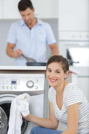 Smiling woman taking cloths from washing machine