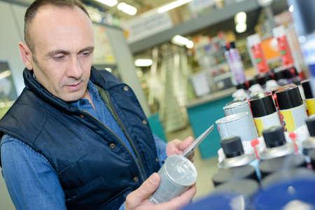 Man customer picking sealing component in household shop Zdjęcie Seryjne