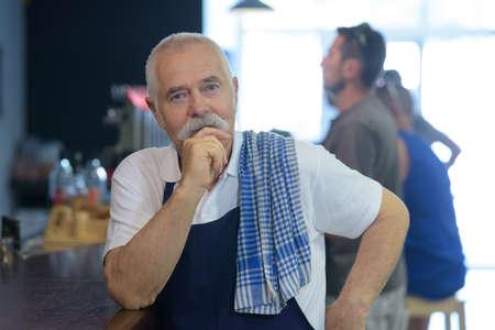 Male senior barista thinking