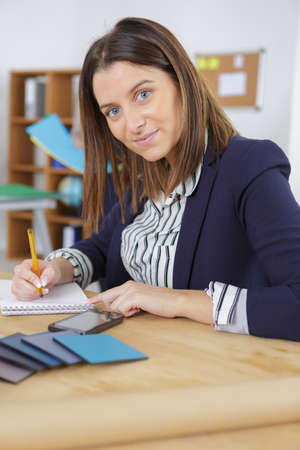 Young female office worker making some notes