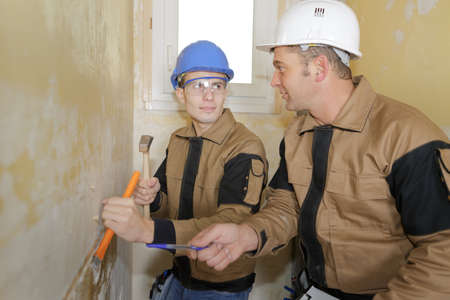 Teacher teaching student to use a chisel and hammer