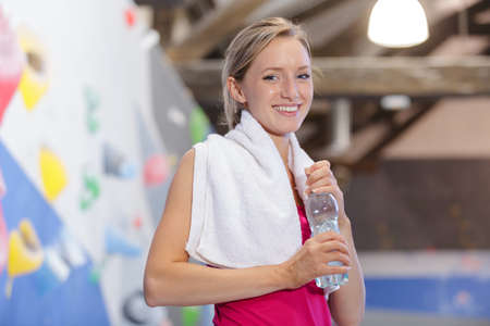 Young woman drinking water after climbing a wall