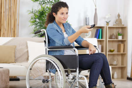 Young woman in wheelchair using remote control