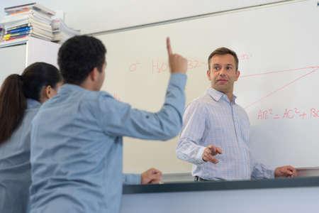 Student raising his hand during class Zdjęcie Seryjne