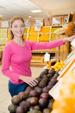 Woman choosing some avocados Standard-Bild