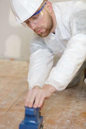 male tradesman sanding wooden floor Banque d'images - 135702458