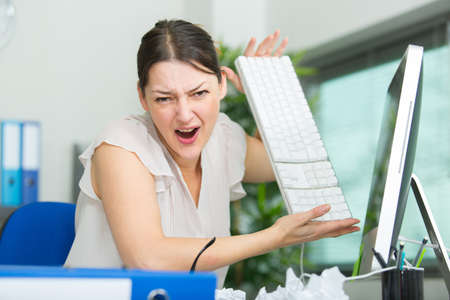 Annoyed and angry woman working on her office desk
