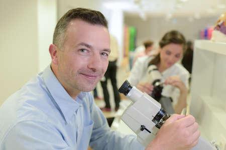 Mature technician looking into microscope