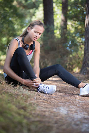 female runner in pain due to sprained ankle