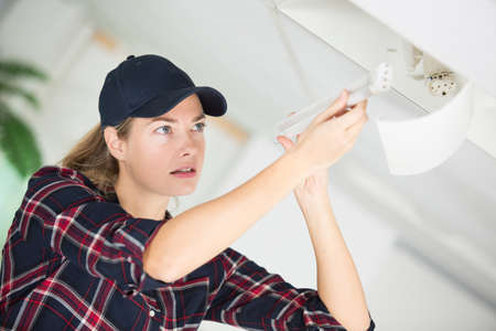 Young woman changing light bulb