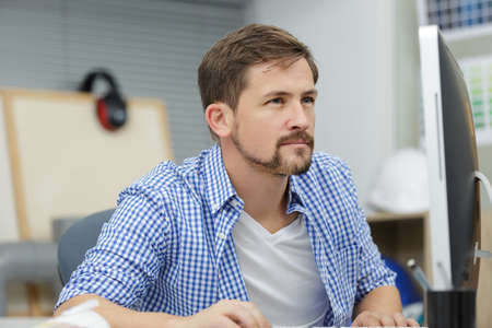 Handsome young man looking on monitor Stock Photo