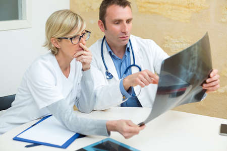 medical workers in office conferring over xray