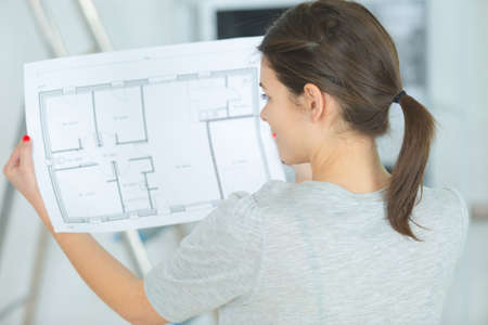 back view of woman holding interior layout plans 写真素材