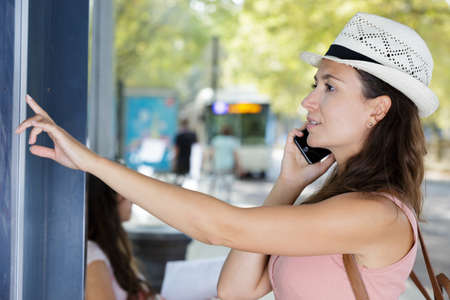 Young woman at bus stop with mobile phone