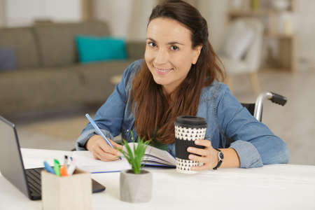 Disabled young woman studying at home