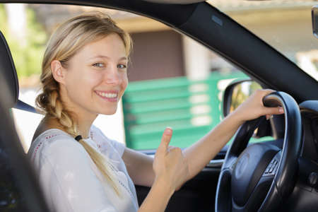 young female driver showing thumbs up Zdjęcie Seryjne